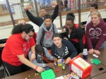 High school students at Carthage High School posing as they build a mock sports goods store out of Legos.