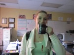 High school student at Pine Tree High School posing with UT Tyler prize mug during recruiting trip.