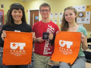 High school students at Pine Tree High School posing with UT Tyler prizes during recruiting trip.