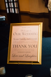 Design for wedding Welcome sign in gold frame, gray lettering on a pale pink background.