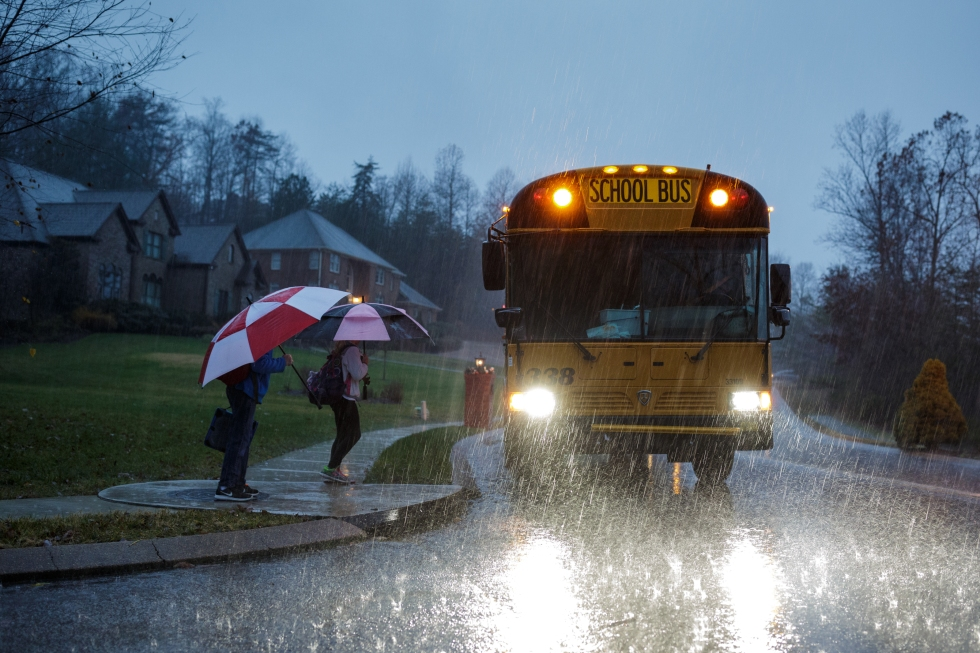 Children waiting in the rain for the bus.